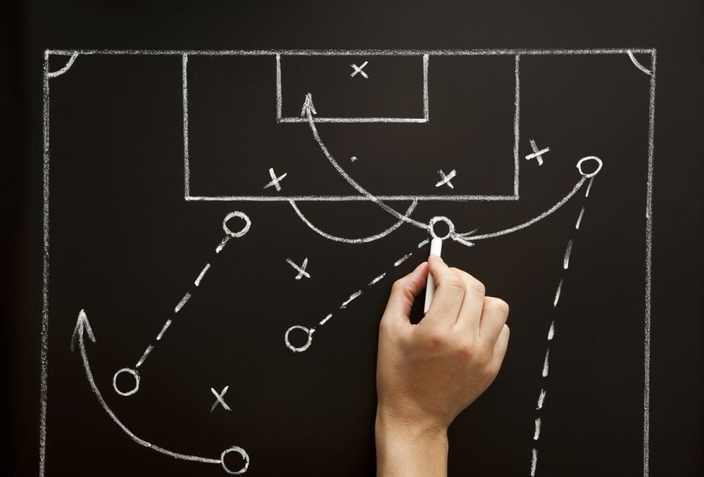 Coach drawing a soccer football game strategy in the locker room ((c) Ivelin Radkov – stock.adobe.com)