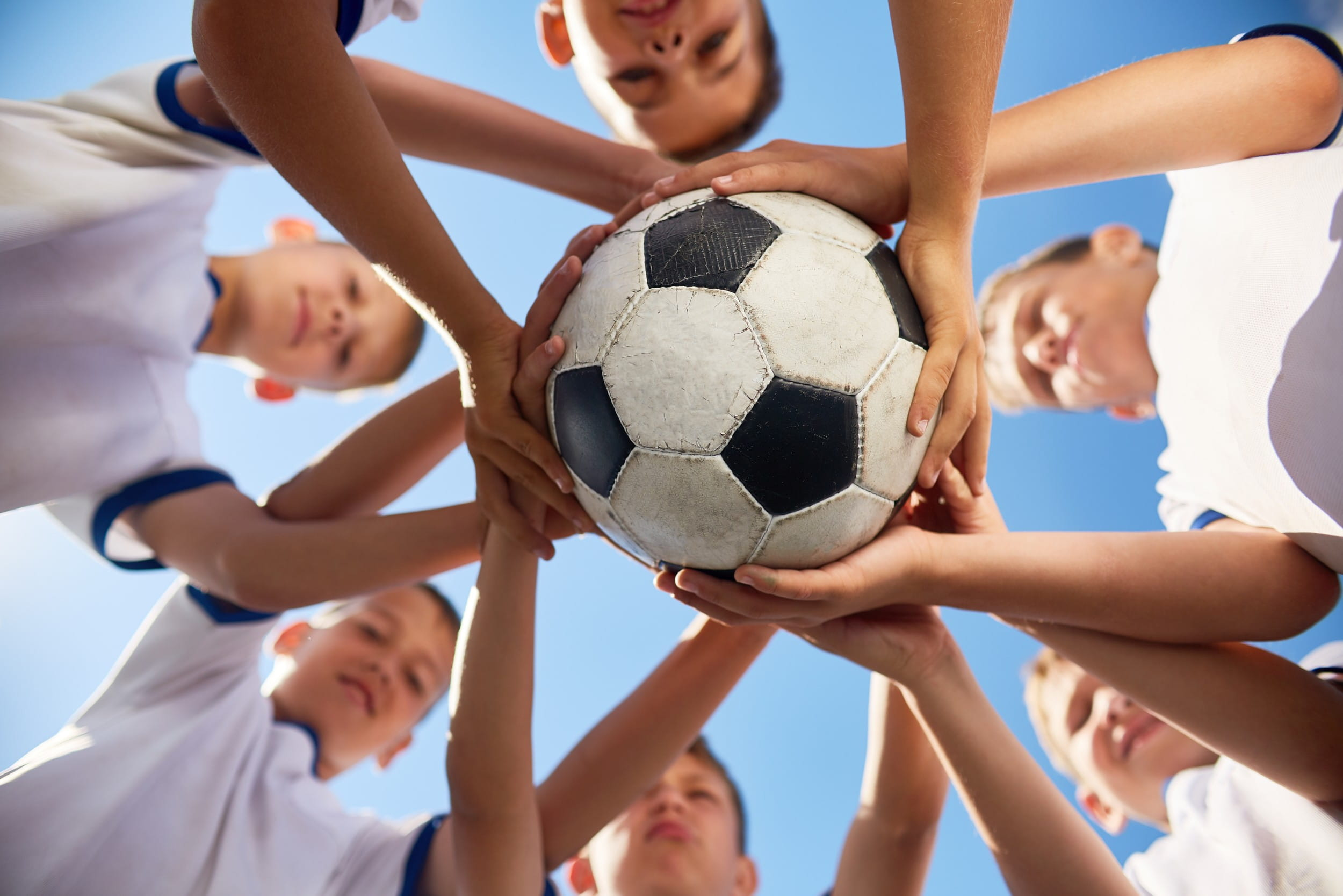 Low angle view of boys in junior football team standing in circle holding ball together against blue sky, focus on ball ((c) Seventyfour – stock.adobe.com)