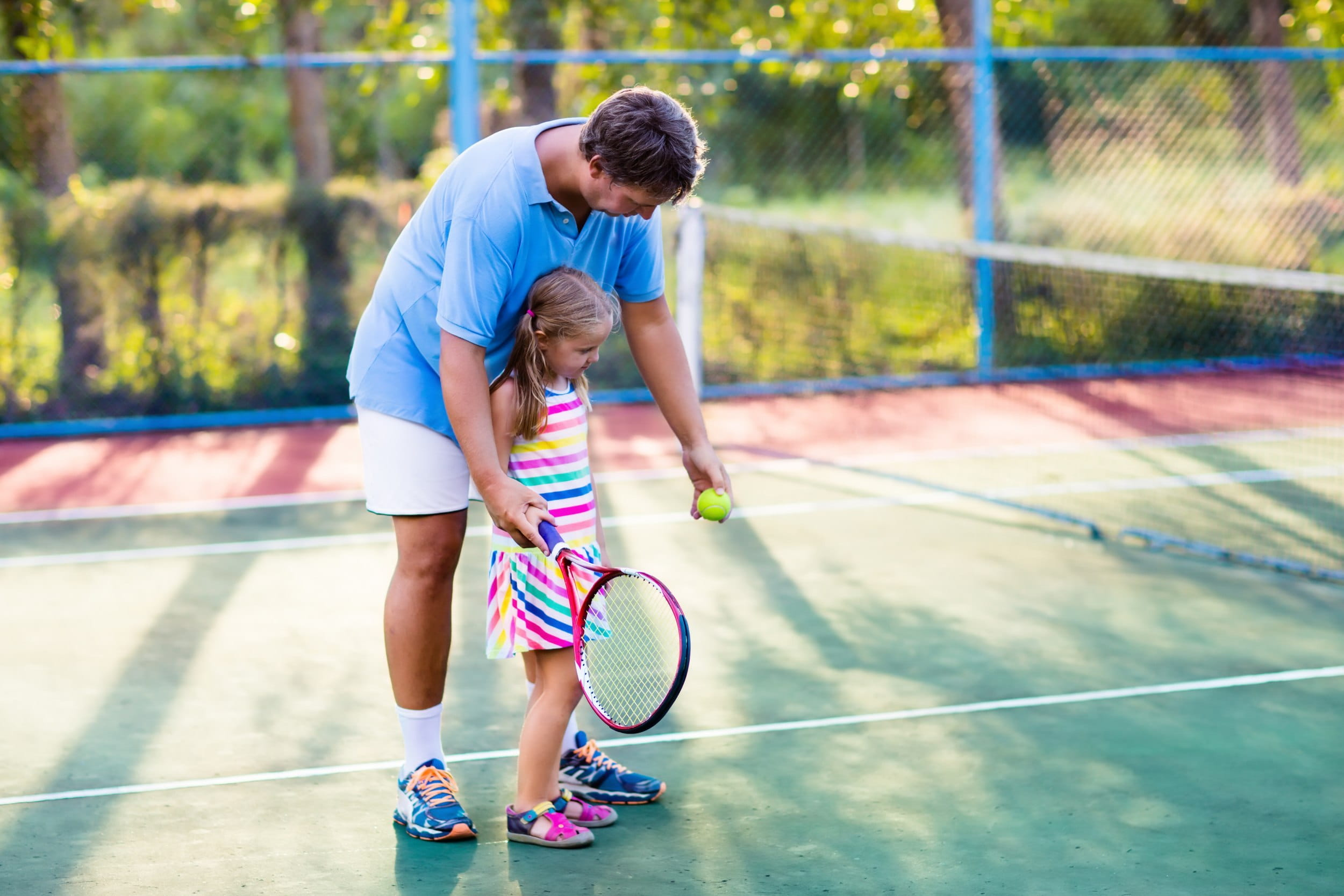 Family playing tennis on outdoor court ((c) famveldman – stock.adobe.com)