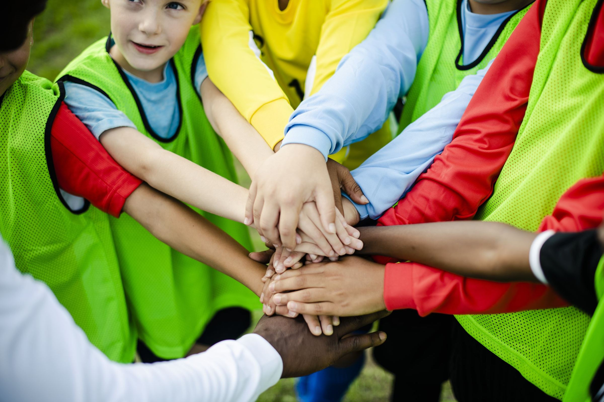 Junior football team stacking hands before a match ((c) Rawpixel.com – stock.adobe.com)