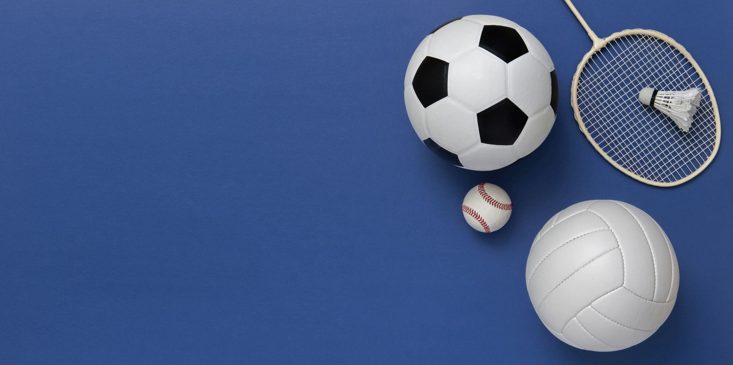 Assorted sports equipment including a basketball, soccer ball, volleyball, baseball, badminton racket on a blue background ((c) Augustas Cetkauskas – stock.adobe.com)