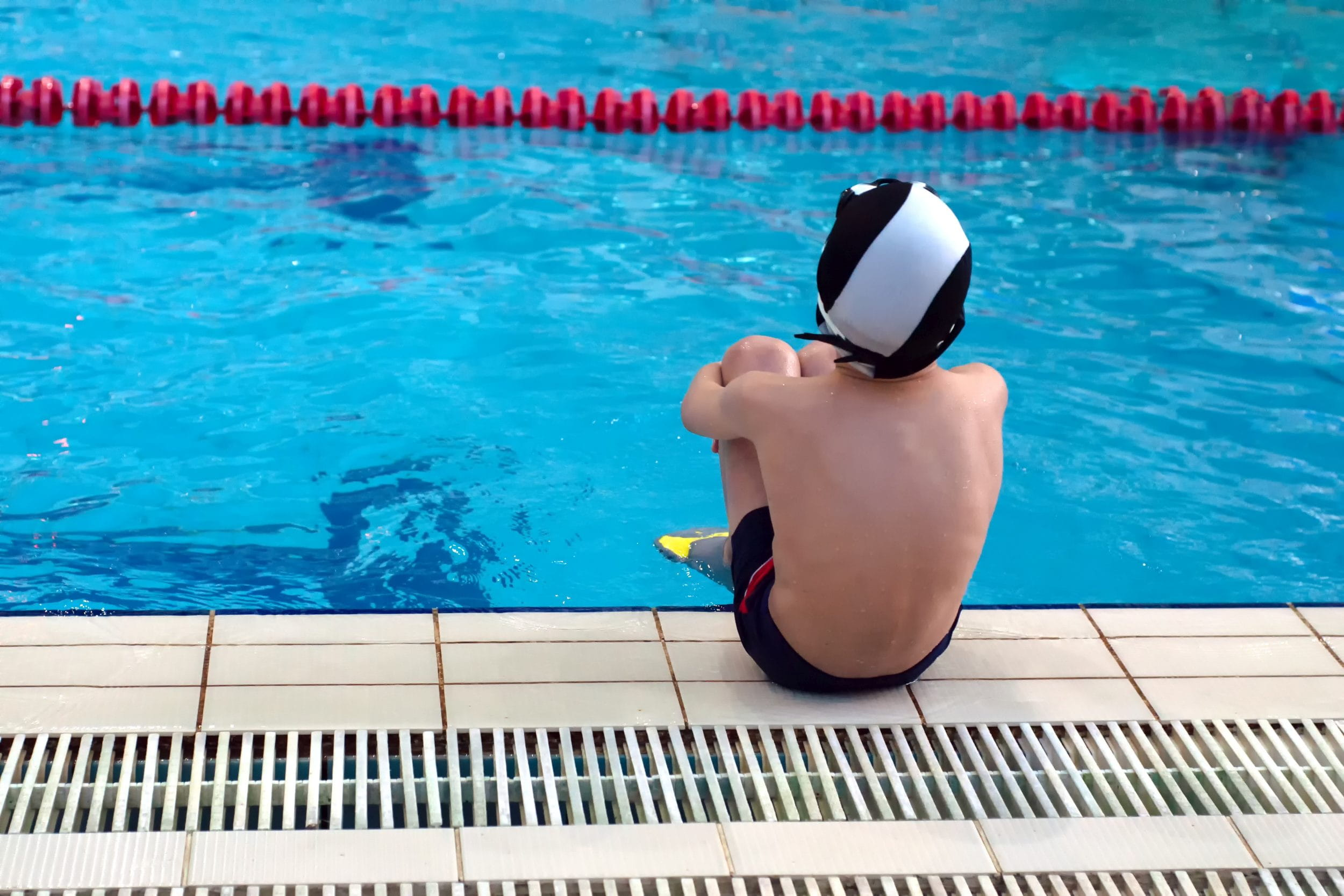 Young boy sitting at the side of the swimming pool looking sad ((c) Yekatseryna – stock.adobe.com)