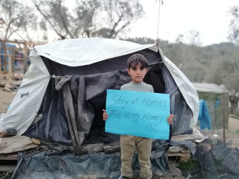 "Ein Junge im Flüchtlingslager Moria auf Lesbos steht vor einem Zelt und hält einen Zettel mit der Aufschrift ""Stay at home! This is my home!"" (Bild: Muhannad, Corona Awareness Team)"