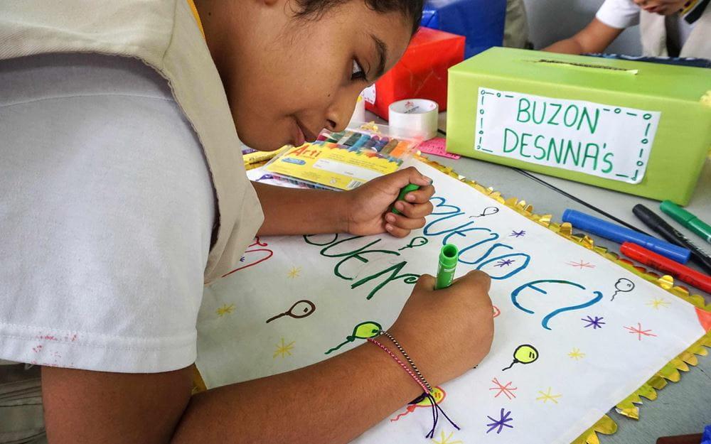 """Reportage Peru: """"Von Selbstvertrauen und Kinderrechten""""; Foto: Kind malt Plakat (Quelle: Lorenz Töpperwien / Kindernothilfe)"""