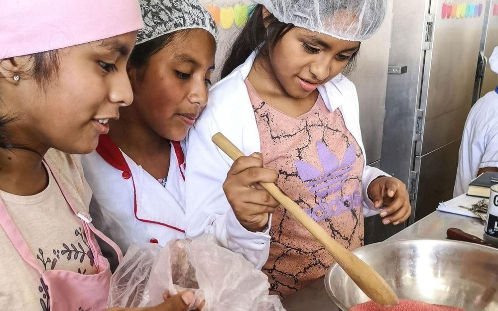 """Reportage Peru: """"Von Selbstvertrauen und Kinderrechten""""; Foto: Kinder arbeiten in der Küche (Quelle: Lorenz Töpperwien / Kindernothilfe)"""