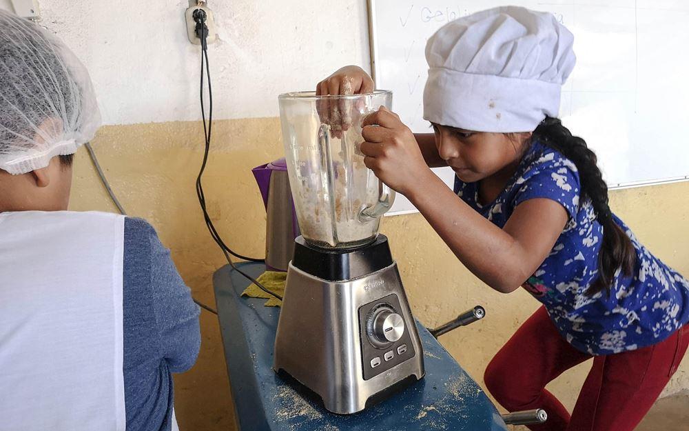 """Reportage Peru: """"Von Selbstvertrauen und Kinderrechten""""; Foto: Zwei Kinder an einer Küchenmaschine (Quelle: Lorenz Töpperwien / Kindernothilfe)"""