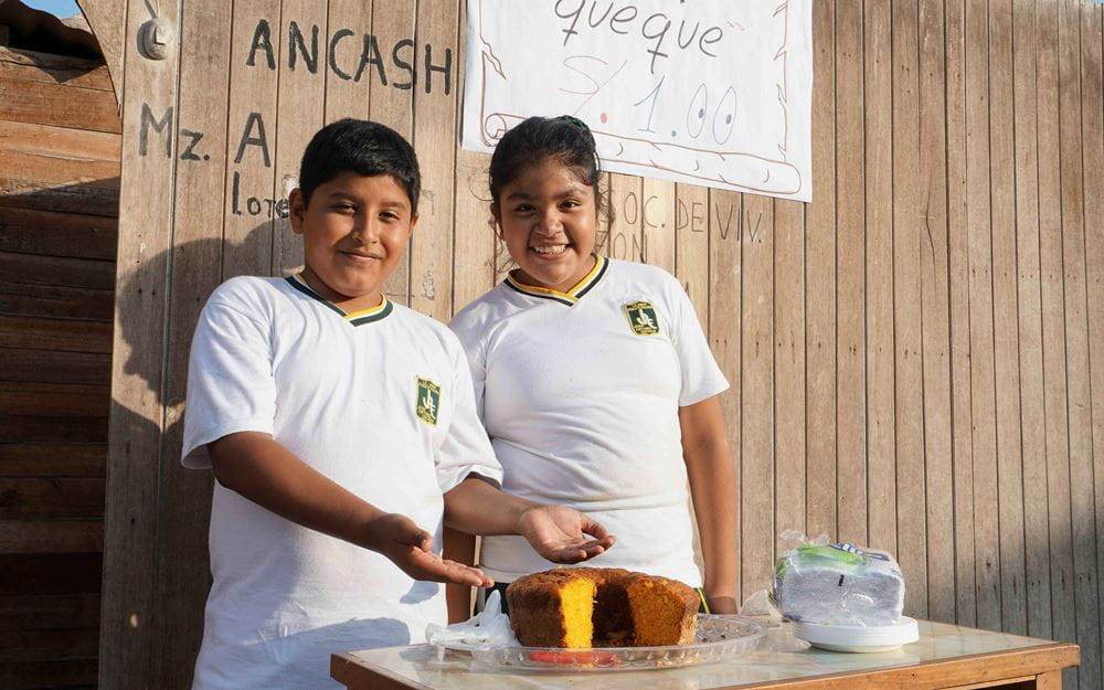 """Reportage Peru: """"Von Selbstvertrauen und Kinderrechten""""; Foto: Zwei Kinder präsentieren Kuchen (Quelle: Lorenz Töpperwien / Kindernothilfe)"""
